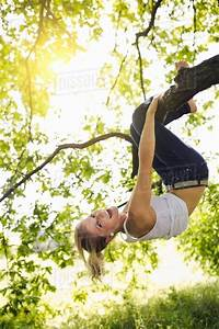 Young, Woman, Hanging, Upside, Down, And, Holding, Onto, Tree