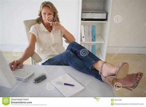 femme au bureau femme d 39 affaires occasionnelle travaillant avec ses pieds